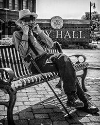 Ken Washburn of Batavia playing one of his harmonicas in the sunny weather of summer in 2016